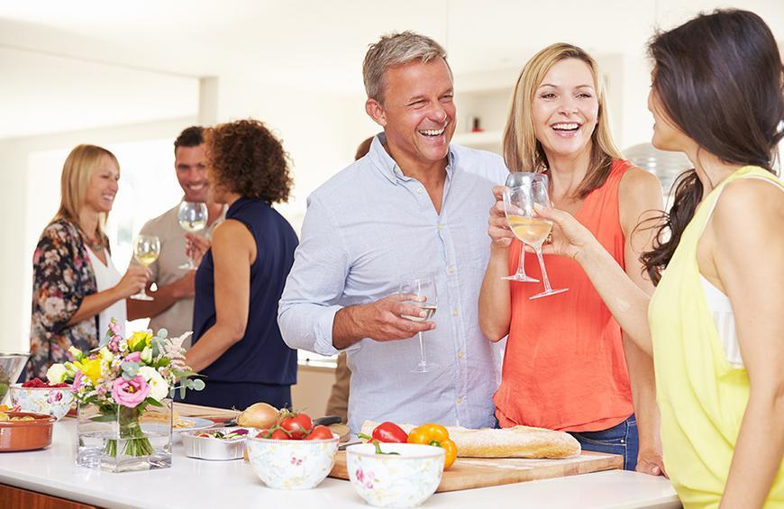 people standing around table of food with wine