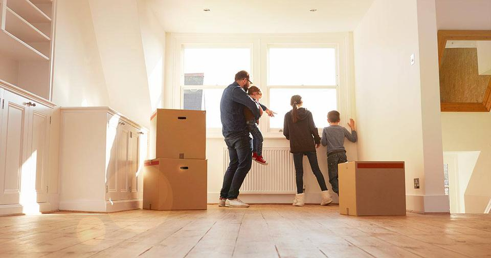 Young family with moving boxes in empty house